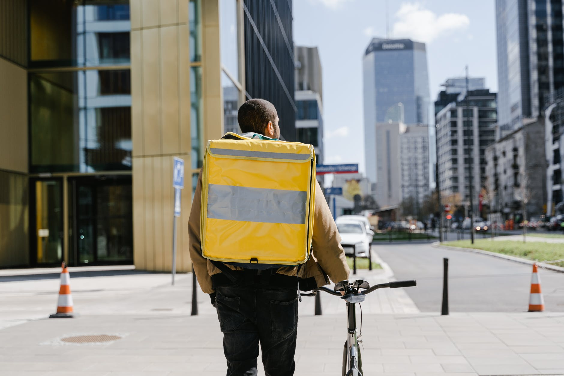 man in yellow jacket and black pants with yellow backpack walking on sidewalk
