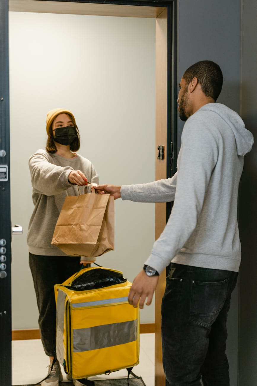man in gray sweater holding a paper bag