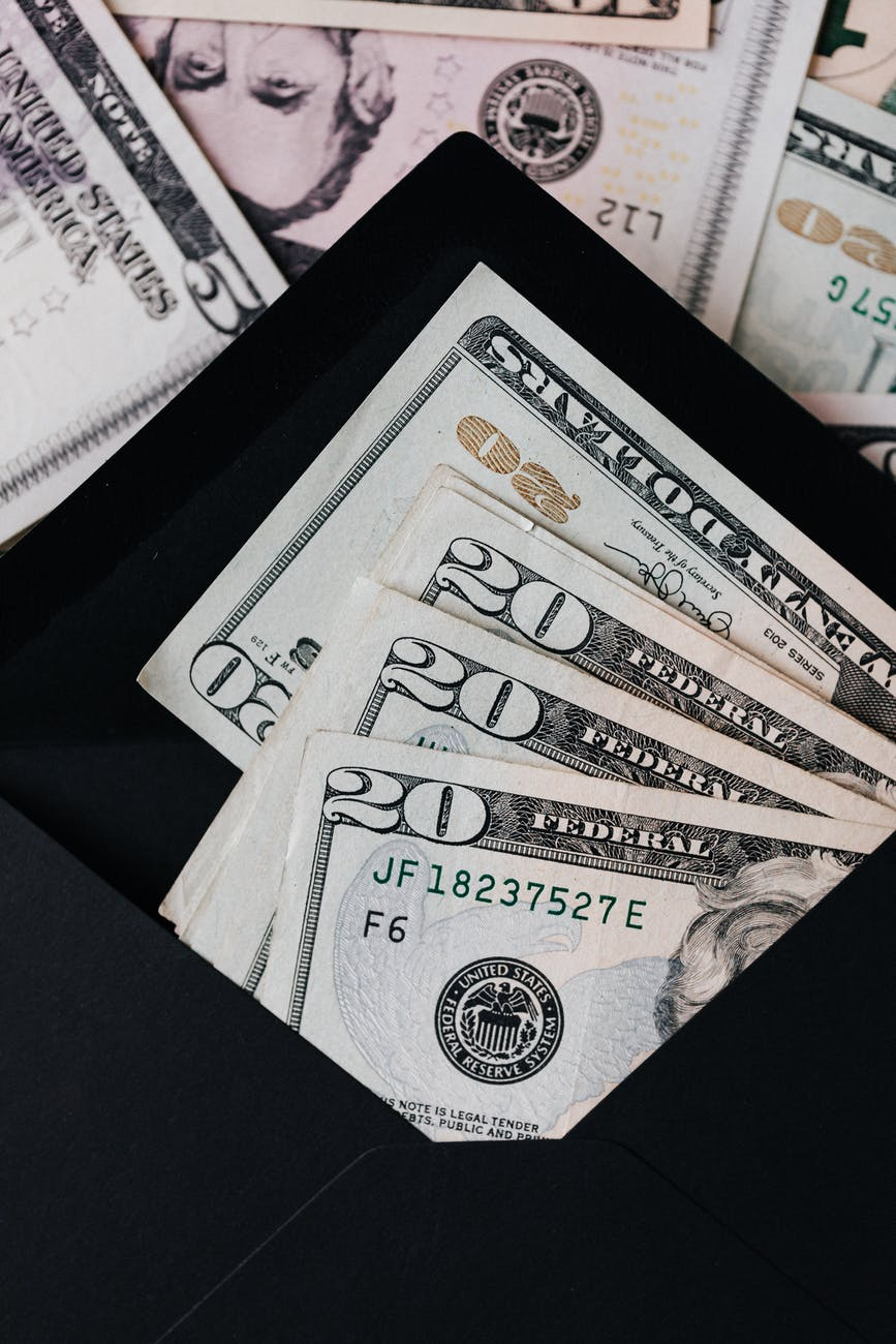 stack of dollars and black envelope with banknotes inside